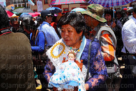 Devotee holding figure of baby Jesus during the Virgen de la Candelaria festival, Puno, Peru