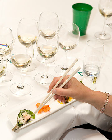 Eating food with chopsticks while tasting wine