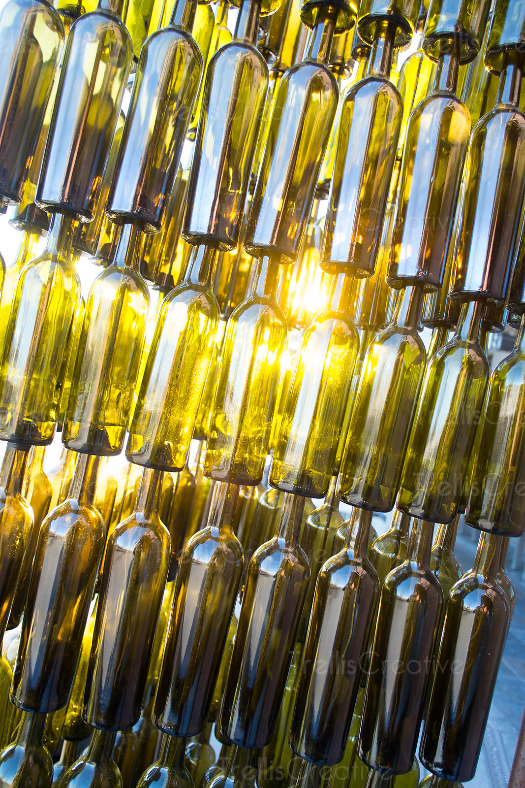 The light shines through a tower of stacked green wine bottles
