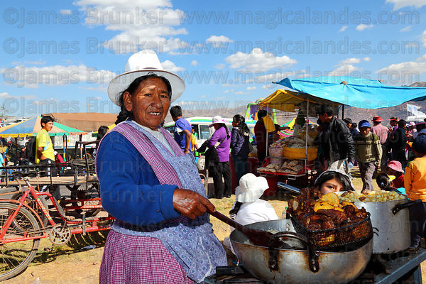 Quechua lady cooking chicharron ( deep fried pork chunks ) , Cusco , Peru