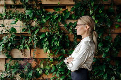 Businesswoman at wall with climbing plants