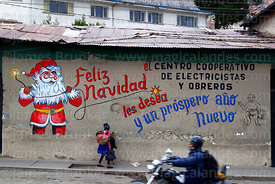 Children and motorbike passing Father Christmas mural on wall of the offices of an electricians and electrical workers cooperative, La Paz, Bolivia