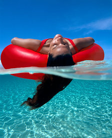 Grand Cayman, Sandbar, under/over, Woman floats on red inter tube with her hair in the water