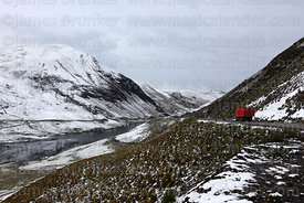Truck and hillside above Incachaca Reservoir near La Paz after winter snowfall, Cordillera Real, Bolivia