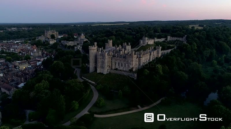 Drone tracks slowly around Arundel Castle and town in the twilight before dawn