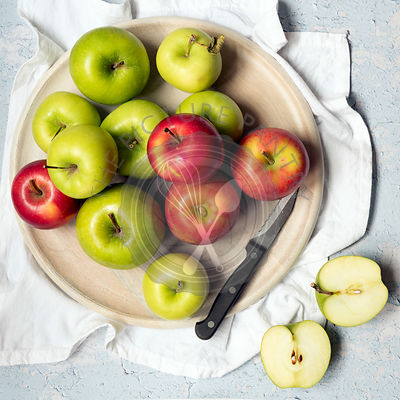 Red and green apples with a knife and two apple halves on a wooden serving board.
