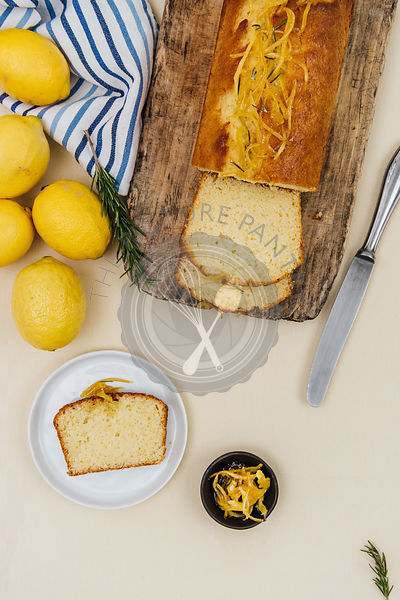 Kefir lemon bread served on a wooden board photographed from top view. Lemons, a slice of the bread on a white plate, lemon zest and a knife accompany.