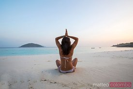 Woman doing yoga at sunrise on the beach, Thailand
