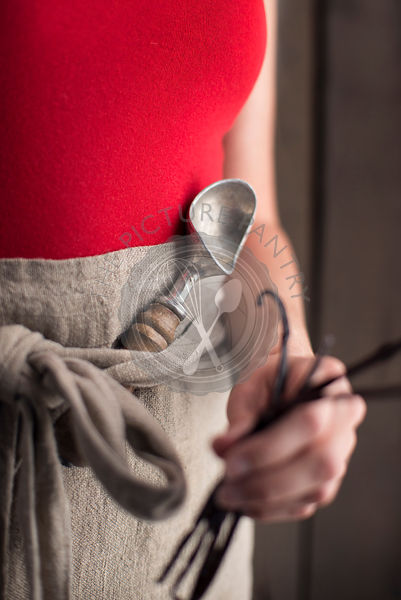 Woman holding vanilla beans with an ice cream scoop tucked into her apron.