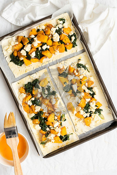 Three uncooked spinach, pumpkin and feta cheese tarts on a baking tray.