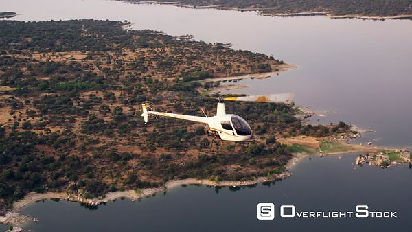 MS small helicopter flying over semiarid landscape and lake, airtoair view, RED R3D 4K