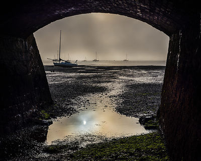 Boats on the Exe estuary in heavy fog viewed through an arch under the Exmouth to Penzance railway line, Starcross, Devon, UK