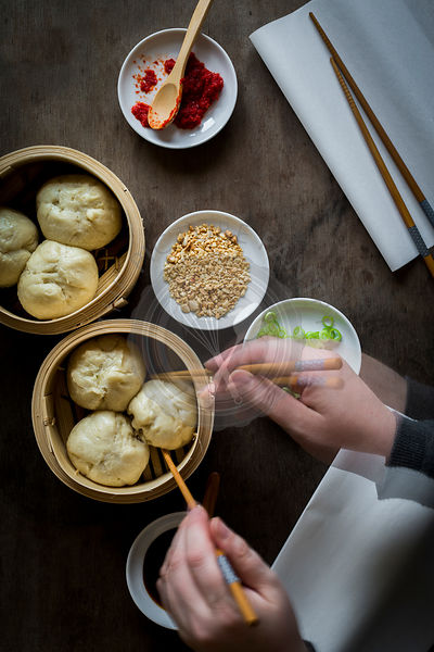 Woman's hands serving steamed dumplings from bamboo steamers on wooden tabletop. Top view