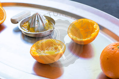freshly squeezed oranges on a silver tray with silver metal hand juicer.