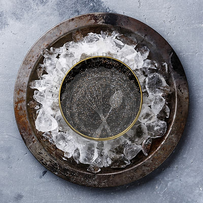 Black Sturgeon caviar in can on ice in metal plate on concrete background