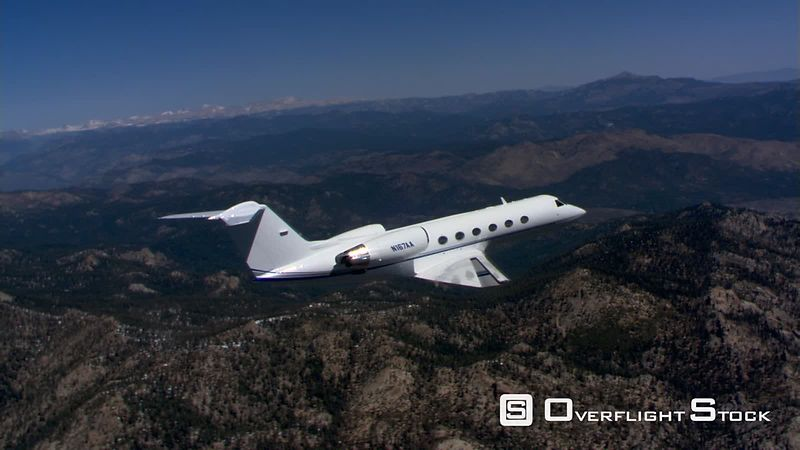Air-to-air side view of small jet above rugged terrain