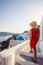 Tourist looking at the beautiful blue domed churches in Oia, Santorini