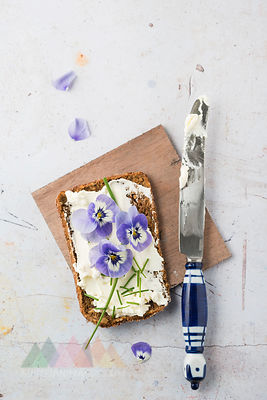 Slice of wholemeal bread with cream cheese, chives and edible Horned Violets