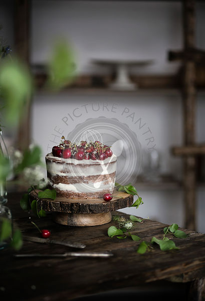 Naked chocolate cake with cherries on wooden table