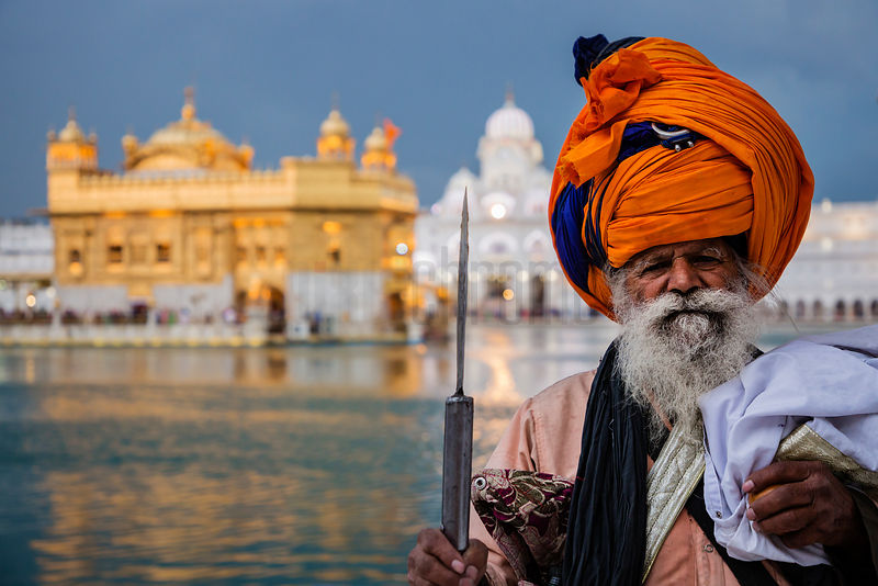 A Nihang Sikh Poses for a Photograph at the Edge of the Sacred Pool at Dusk