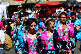Caporales dancer checking text messages while dancing at Gran Poder festival, La Paz, Bolivia