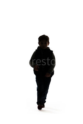A silhouette of a boy walking - shot from mid level.
