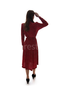A semi-silhouette of a 1940's woman in a red dress looking away – shot from eye-level.