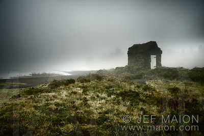 Stone hut and lake in fog
