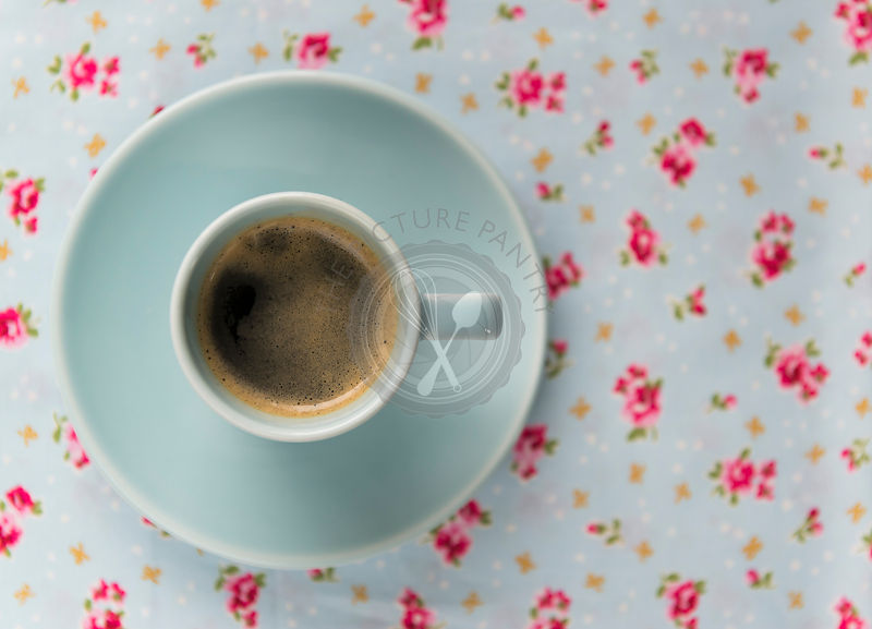 Espresso coffee in a blue cup and saucer on a floral table cloth.