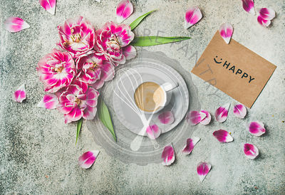 Flat-lay of cup of coffee surrounded with pink tulip flowers and sign happy on paper over grey marble background