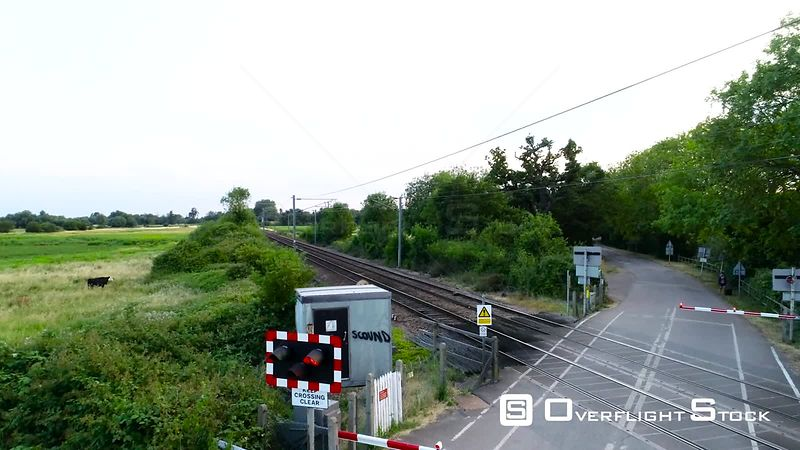 Aerial view of closed and open railway level crossing with passing train filmed by drone in summer, United Kingdom