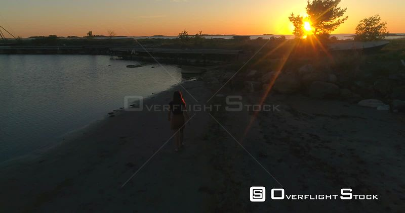 Girl walking at the sea, aerial view following a woman, enjoying sun glimps on her skin and a warm summer sunset, on a sunny evening dusk, in Hanko, Uusimaa, Finland