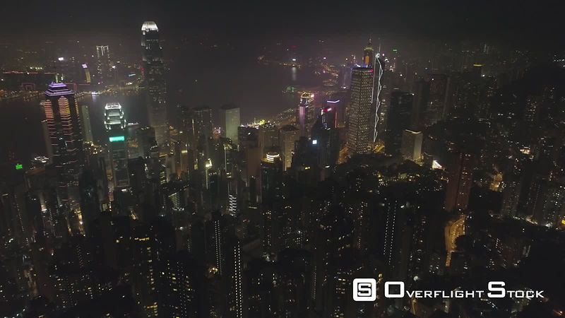 Illuminated Hong Kong Skyline and Victoria Harbour at Night. Aerial View. Drone is Flying Forward, Camera is Tilting Up. Establishing Shot. 60 fps.