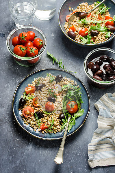 Farro spelt salad with cherry tomatoes,black olives and arugula