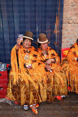 Cholitas drinking at street party after formal parades, Virgen de la Candelaria festival, Puno, Peru