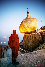 Buddhist monk standing in front of the Golden rock at sunrise