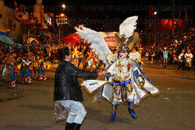 A female spectator dances with the Archangel Michael during the Diablada dance at night, Oruro Carnival, Bolivia