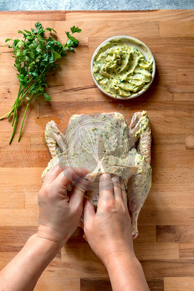Woman's hands rubbing a raw chicken with herb butter.Top view