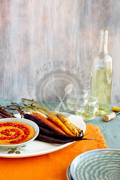 Sumac Roasted Carrots with Roasted Red Pepper Harissa Pesto. Photographed on a green background.