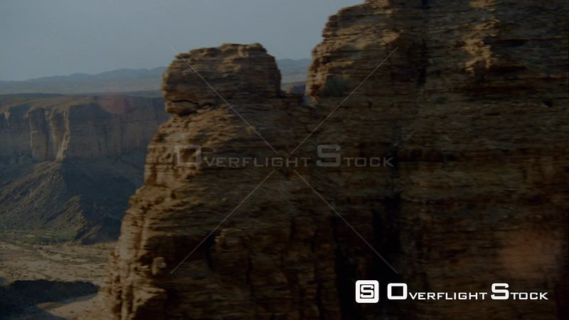 Aerial side of rocky outcrop and single weathered pillar of rock, wide long shot dry riverbed in desert terrain and mountain range in background Fish River Canyon Namibia