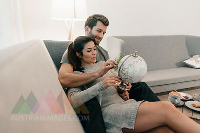 Couple relaxing on couch at home looking at globe