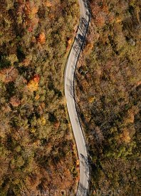 Aerial photograph of a curvy road in the mountains of West Virginia with fall foliage.