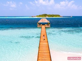 Aerial view of woman walking on jetty, Maldives