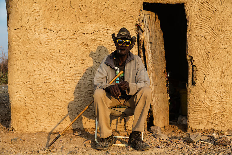 Portrait of a Herero Man with Yellow Glasses, a Straw Hat and a Pipe