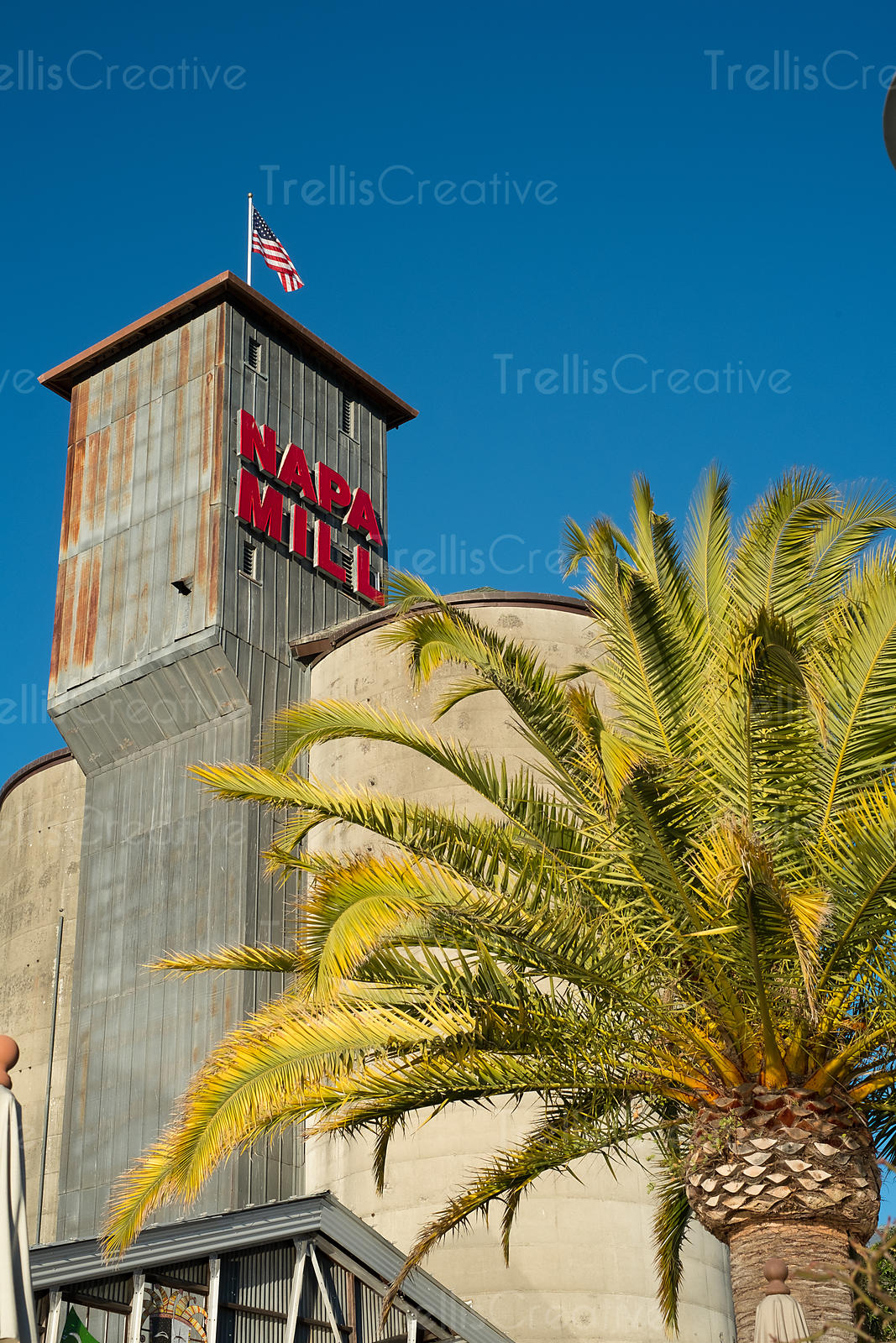 Exterior of the Napa Mill with a palm tree and the American flag flying high