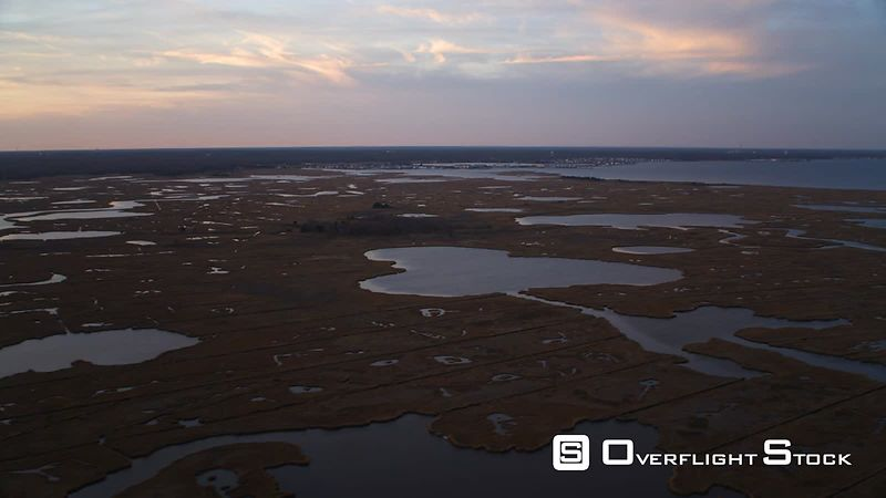 Flying over marshy islands at dusk with Barnegat, New Jersey in background. Shot in November