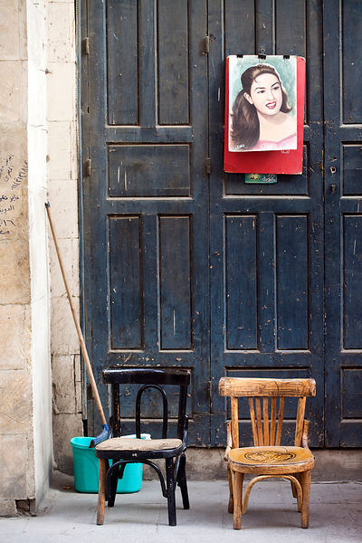 Egypt - Cairo - A picture of a woman and two chairs on the street, Bein al-Qasreen area, Islamic Cairo