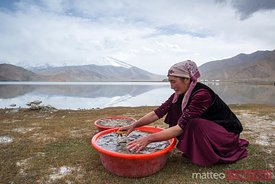 Kyrgyz woman washing wool near the shores of Karakol lake