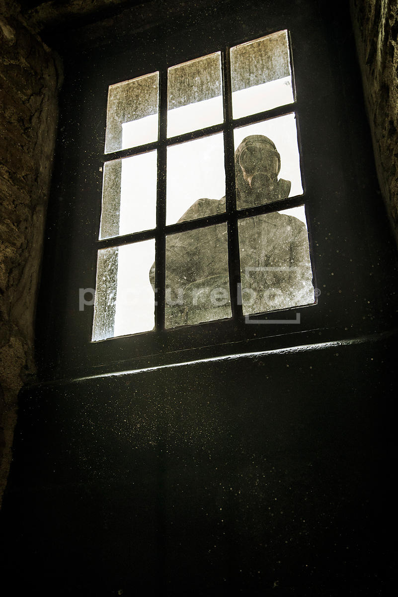 An image of a man in a chemical suite and gas mask, looking through a dirty old window, into a dusty room.