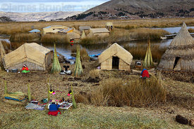 Aymara lady setting up souvenir stall on Uros floating reed islands , Lake Titicaca , Peru